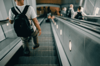 man wearing backpack walking down escalator